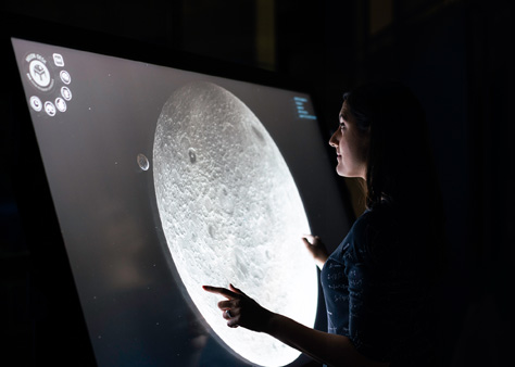 A woman in front of a screen with a graphic of the moon on it