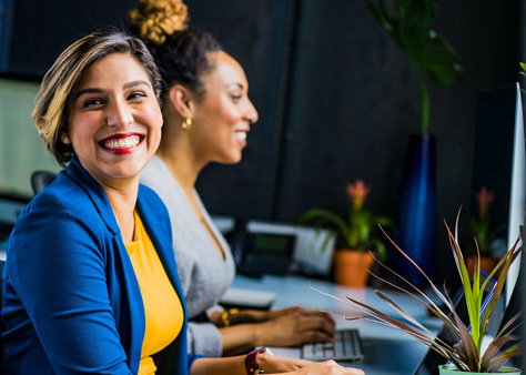 Two women sitting at computers. One woman is smiling at the camera
