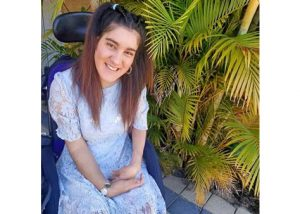 Image shows a smiling woman sitting in a wheelchair. She is wearing a blue dress.